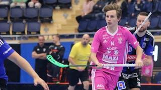 Faluns Malte Lundmark i rosa matchställ till höger i bild. Lundmark håller klubban med båda händer i midjehöjd och bakom honom syns en Siriusspelare och en domare.