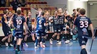 Mullsjöspelarna har precis lämnat sin bänk och står uppradade efter ett mål. Centralt i bild ger Gustav Svensson sin lagkamrater en high-five.