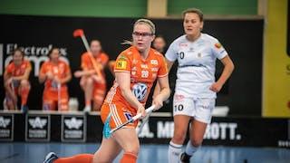 IKSU:s Veera Kauppi, iklädd hemmalagets organgea dress, fångad i steget med båda händerna på klubban. Snett bakom hennes syns Göteborgs Victoria Wallenstam.