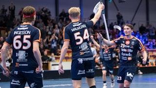 Mullsjös Sebastian Palmqvist höjer klubban och går fram mot lagkamraten Oskar Malmgren som är vänd med ryggen mot kameran. Till vänster i bild syns Joel Ingesson, även han vänd med ryggen mot kameran.