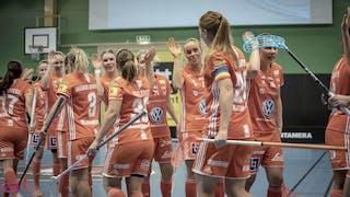 IKSU-spelarna står uppställda i två rader och ger varandra en high-five vid det ena målet. I bakgrunden syns läktare med publik.